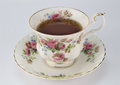 Full antique teacup and saucer with rose and gold decoration iso Royalty Free Stock Photo