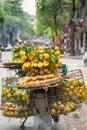 Full basket of orange fruit on vendor bike on Hanoi street, Vietnam