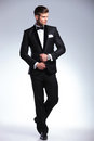 Full body of a business man looking away length picture an elegant young fashion adjusting his tuxedo while to his side from the Royalty Free Stock Photo