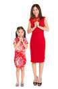 Full body chinese parent and child greeting to each other happy new year in traditional cheongsam isolated on Royalty Free Stock Images
