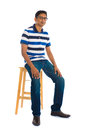 Full body indian man sitting on a chair over white background photo Stock Images