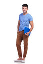 Full body picture of a young casual man holding notepad