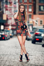 full body portrait of young beautiful woman walking on city street wearing sexy short dress Royalty Free Stock Photo