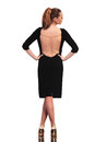 Full body rear view of a sexy blonde business woman standing on studio background with her hands on her waist Royalty Free Stock Image