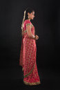Full body side view of traditional young indian girl or profile in sari costume standing isolated on black background Royalty Free Stock Images