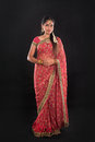 Full body traditional indian girl in sari costume standing isolated on black background Stock Photo