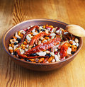 Full bowl of different haricot beans and red hot chilli peppers on the wooden table Royalty Free Stock Photos