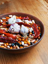 Full bowl of different haricot beans red hot peppers and garlic on the wooden table Stock Photography