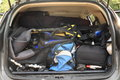 Full car trunk of a silver of things diving equipment bags and guitar Royalty Free Stock Photography