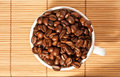 Full cup with coffee beans on the table Royalty Free Stock Photo