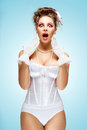 Full of emotions the retro photo a shocked and surprised bride with stylish makeup in a vintage corset showing strong Stock Photography