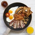 Full English breakfast in a pan with fried eggs, bacon, sausages, beans, toasts and orange juice on white wooden surface, overhead Royalty Free Stock Photo