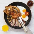Full English breakfast in a pan with fried eggs, bacon, sausages, beans, toasts and orange juice on white wooden surface, top view Royalty Free Stock Photo
