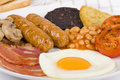 Full english breakfast traditional fry up with egg bacon mushrooms tomatoes sausages black pudding hash browns and baked beans Stock Image