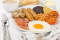 Full english breakfast traditional fry up with egg bacon mushrooms tomatoes sausages black pudding hash browns and baked beans Stock Images