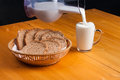 Full glass of milk poured from a jug near the a basket bread on wooden table Royalty Free Stock Photography