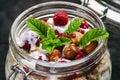 Full jar of muesli, yogurt, raspberries, nuts on a black, burnt wood table. Homemade breakfast cereals food. Healthy eating Royalty Free Stock Photo