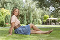 Full length of beautiful young woman looking away while relaxing on grass in park Royalty Free Stock Photo