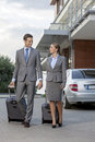 Full length of business couple with luggage walking outside hotel Stock Images
