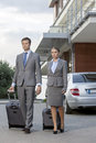 Full-length of business couple with luggage walking outside hotel Royalty Free Stock Photo