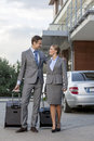 Full length of business couple walking with luggage outside hotel Royalty Free Stock Image