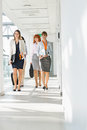 Full-length of businesswomen walking at office hallway Royalty Free Stock Photo