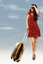 Full length of casual woman standing with travel suitcase Royalty Free Stock Image
