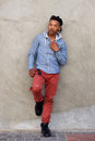 Full length cool african man with dreadlocks leaning against wall Royalty Free Stock Photo