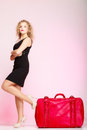 Full length elegant lady in voyage, traveler woman with old red bag Royalty Free Stock Photo