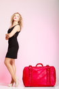 Full length elegant lady in voyage traveler woman with old red bag of young suitcase luggage on pink background travel theme Stock Photo
