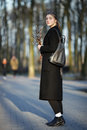 Full length emotional portrait of young happy beautiful woman with a bouquet of pussy-willows wearing black coat strolling at even