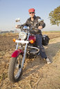 Full length european biker India hinterlands Royalty Free Stock Photography