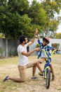 Full length of father and son doing high five in yard Royalty Free Stock Photo