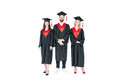 Full length front view of happy students in graduation caps standing together Royalty Free Stock Photo