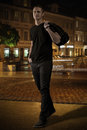 Full length handsome smiling young man walking old town street night bag Stock Photos