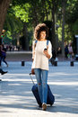 Full length happy woman walking in park with suitcase and mobile phone Royalty Free Stock Photo