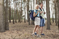 Full length of happy young couple hiking in forest Stock Photos