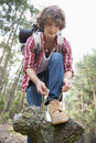 Full length of male backpacker tying shoelace in forest Stock Photo