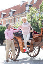 Full length of middle aged man assisting woman out of horse cart men women Stock Image