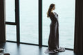 Full length of pensive woman in knitted coverlet enjoying view Royalty Free Stock Photo