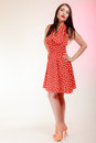 Full length pinup girl brunette woman in retro red dress vintage style of beautiful stylized young attractive spotted on pink Stock Photos