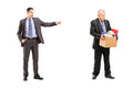 Full length portrait of an angry boss firing an employee isolated on white background Stock Images