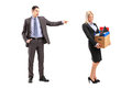 Full length portrait of an angry boss firing a women with a box of her personal items isolated on white background Royalty Free Stock Images
