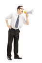 Full length portrait of an angry businessman shouting via megaph megaphone isolated on white background Stock Images