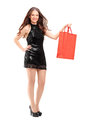 Full length portrait of an attractive young woman holding a shopping bag isolated on white background Stock Photos