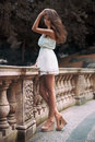 Full length portrait of beautiful model woman with long legs wearing white dress posing oudoors Royalty Free Stock Photo