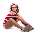 Full length portrait beautiful young positive american patriotic girl wearing red shorts off shoulder usa flag top tank sitting Royalty Free Stock Photos