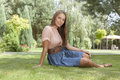Full length portrait of beautiful young woman in casuals relaxing in park Royalty Free Stock Photos