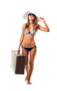 Full length portrait of a beautiful young woman posing in a biki bikini hat and sunglasses with suitcase hand on white background Stock Photos