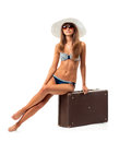 Full length portrait of a beautiful young woman posing in a biki bikini sitting on suitcase on white background Royalty Free Stock Image